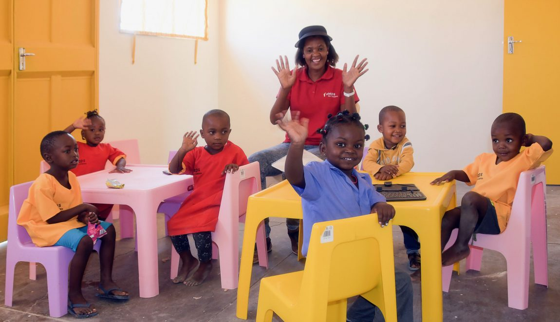 steps-Mitarbeiterin & Kinder im neu bezogenen Klassenraum